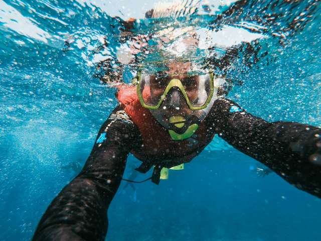 Woman taking a selfie underwater while getting a diving lesson for free as a promotional gift