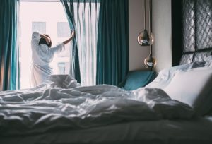 Woman opening a curtain in a hotel room after getting up in the morning, enjoying her free hotel stay