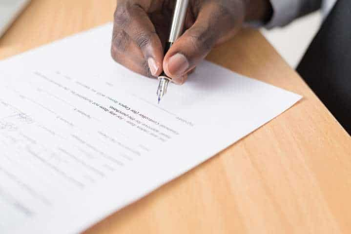 Close up of a hand signing a telecom contract after hearing about the free flight promotion