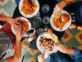 Four friends enjoying burgers and after redeeming a culinary reward voucher